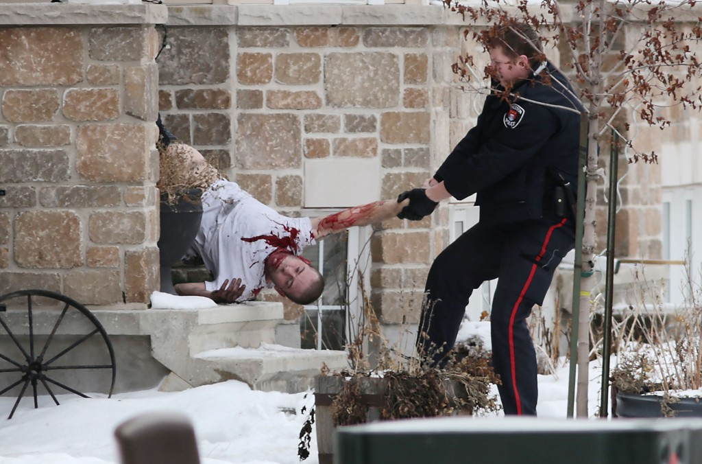 Kingston police carry an injured man from a townhouse after a standoff and fire (Elliot Ferguson/Kingston Whig-Standard)