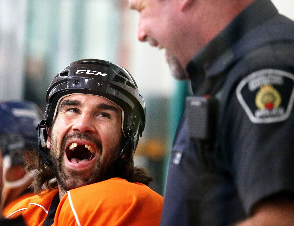 Zack Stortini shares a laugh with constable Scott Mills during the Special Olympics torch run hockey game in Sudbury, August 4, 2015 (Gino Donato/Sudbury Star)