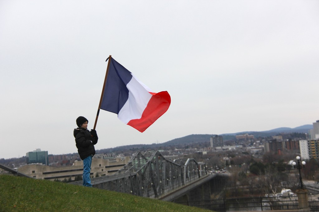 How far away home must have felt for French families living in Canada after the November 13th Paris attacks. A French child, alone on a hill in Ottawa, waving the flag of his country symbolizes that distance (Haley Ritchie/Metro Ottawa)