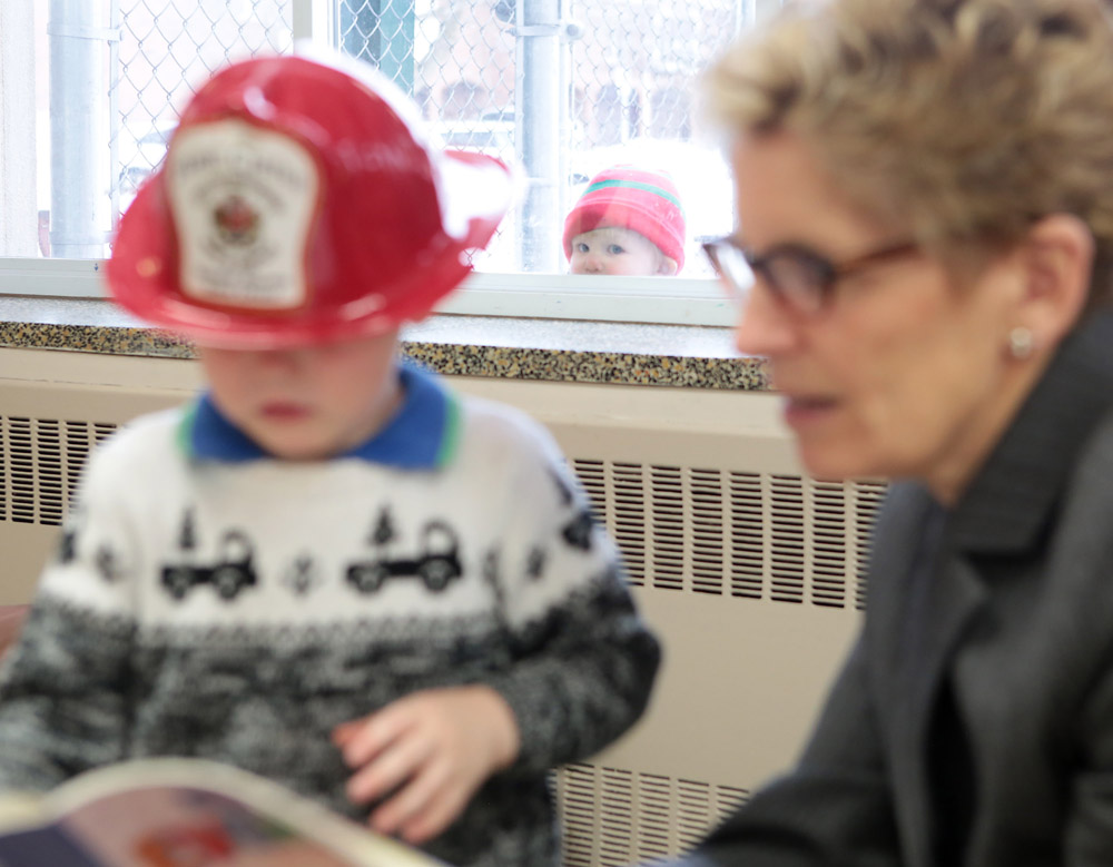 Ontario Premier Kathleen Wynne reads to Jacob Claessen, 2, while Duncan Kerry, 2, looks in from the outside at the child care centre at the YMCA of Kingston (Elliot Ferguson/Kingston Whig-Standard)